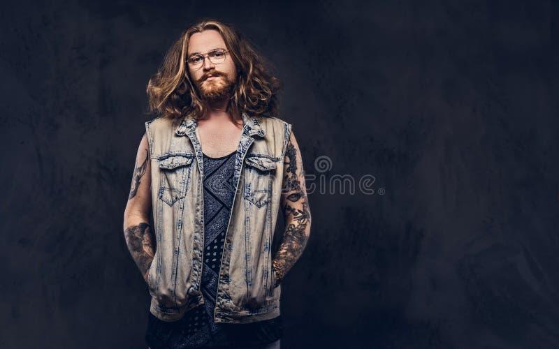 Het roodharige hipster mannetje met lang luxuriant haar en volledige baard gekleed in vrijetijdskleding die stellen met dient zak stock foto