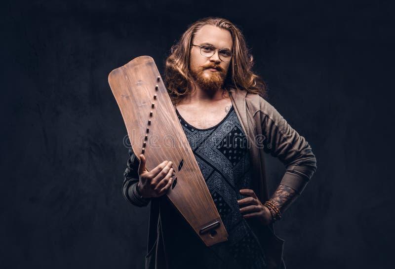 Het roodharige hipster mannetje met lang luxuriant haar en volledige baard gekleed in vrijetijdskleding houdt een Rus traditionee royalty-vrije stock afbeelding