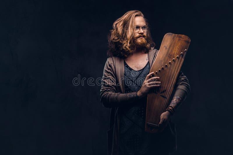 Het roodharige hipster mannetje met lang luxuriant haar en volledige baard gekleed in vrijetijdskleding houdt een Rus traditionee royalty-vrije stock foto