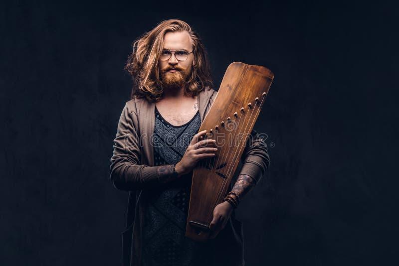 Het roodharige hipster mannetje met lang luxuriant haar en volledige baard gekleed in vrijetijdskleding houdt een Rus traditionee royalty-vrije stock fotografie
