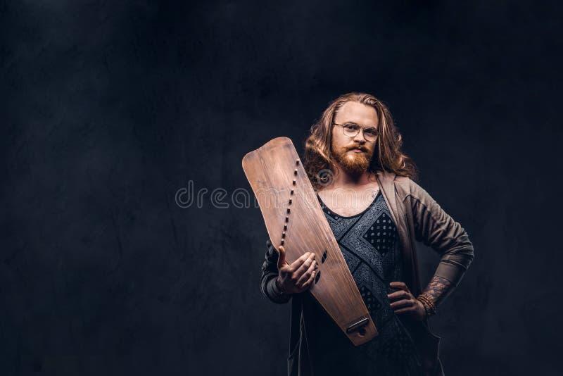 Het roodharige hipster mannetje met lang luxuriant haar en volledige baard gekleed in vrijetijdskleding houdt een Rus traditionee stock fotografie