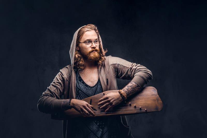 Het roodharige hipster mannetje met lang luxuriant haar en volledige baard kleedde zich in een hoodie en t-shirt het spelen op ee stock foto's