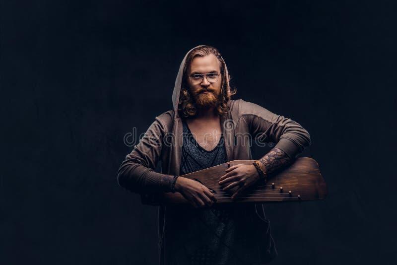 Het roodharige hipster mannetje met lang luxuriant haar en volledige baard kleedde zich in een hoodie en t-shirt het spelen op ee stock afbeeldingen