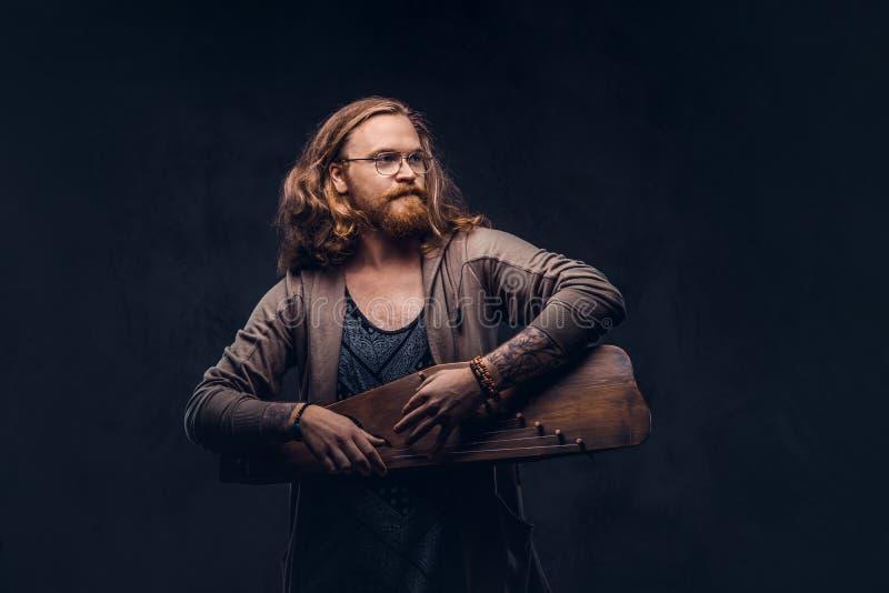 Het roodharige hipster mannetje met lang luxuriant haar en volledige baard kleedde zich in vrijetijdskleding spelend op een tradi stock afbeelding