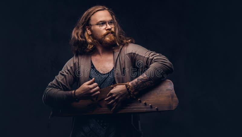Het roodharige hipster mannetje met lang luxuriant haar en volledige baard kleedde zich in vrijetijdskleding spelend op een tradi stock afbeeldingen