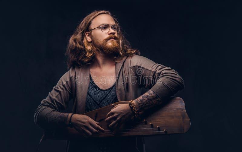 Het roodharige hipster mannetje met lang luxuriant haar en volledige baard kleedde zich in vrijetijdskleding spelend op een tradi stock foto's