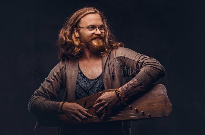 Het roodharige hipster mannetje met lang luxuriant haar en volledige baard kleedde zich in vrijetijdskleding spelend op een tradi royalty-vrije stock foto