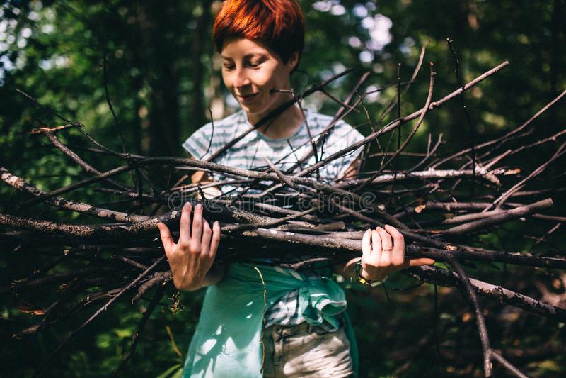 Het roodharige hipstermeisje verzamelt brandhout op de achtergrond van het bos stock foto