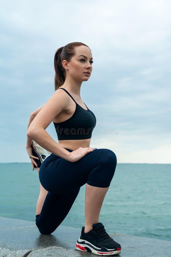 Het roodharige, jonge, atletische, mooie meisje nam in gymnastiek, looppas in openlucht in dienst Voert sportenoefeningen voor ui royalty-vrije stock foto's
