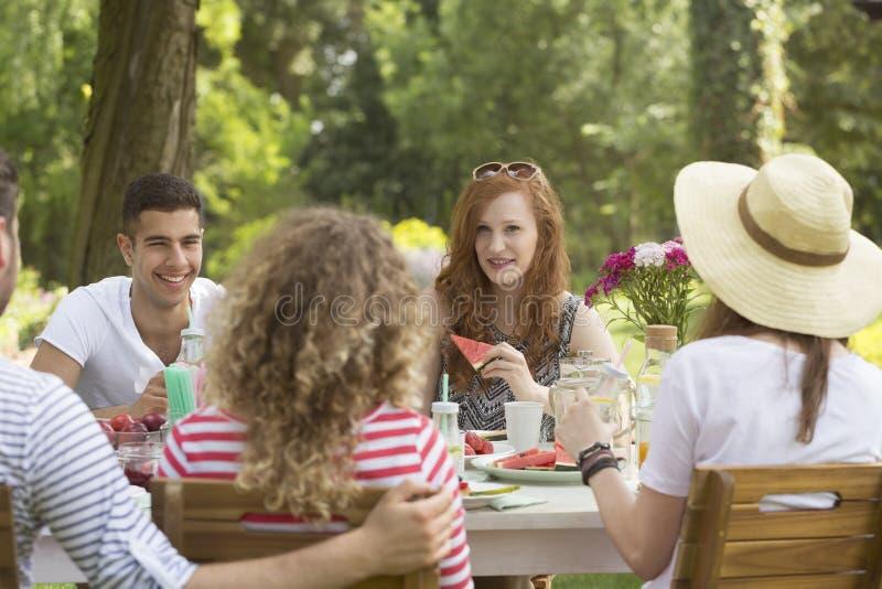 Het roodharige meisje die watermeloen eten tijdens tuinpartij met frien stock afbeeldingen