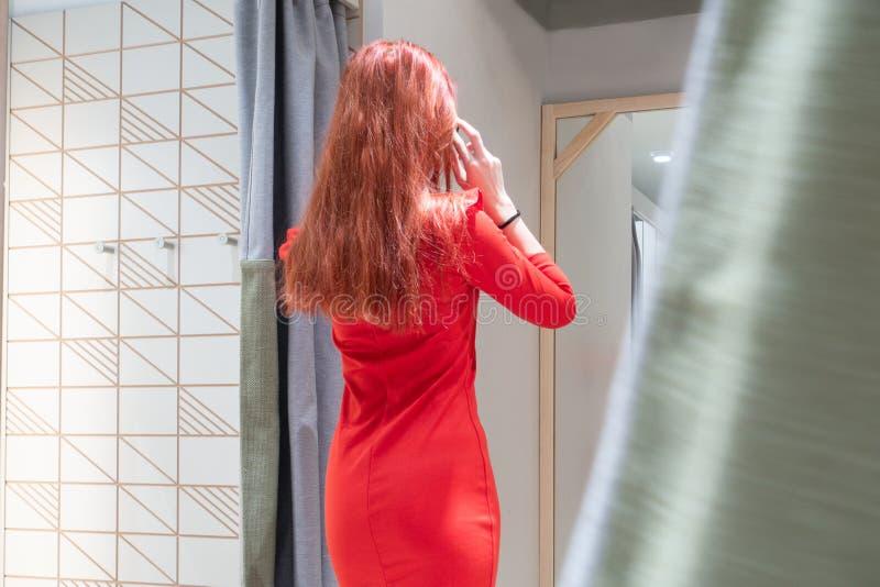 Het roodharige meisje in een rode kleding kijkt in de spiegel wijfje in een montageruimte voor kleren mening van het achter, slan stock afbeelding