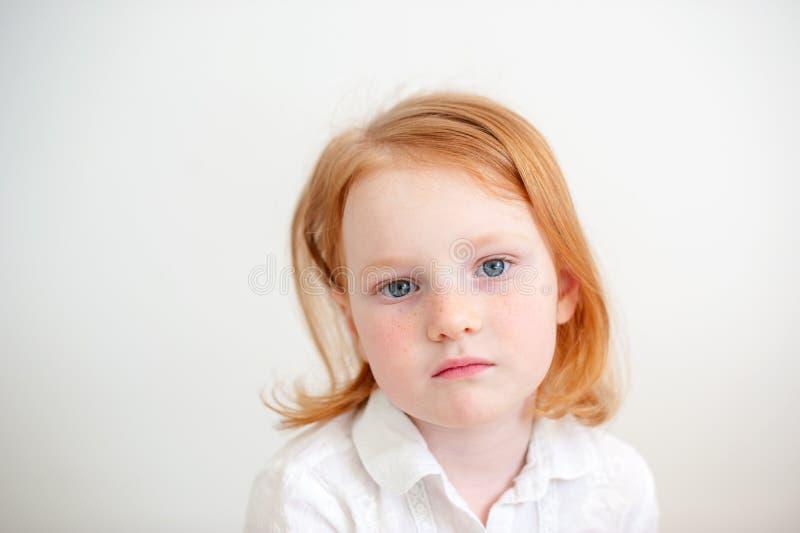 Het roodharige meisje kijkt zorgvuldig stock foto