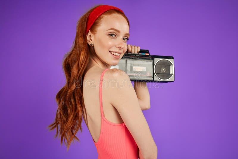 Het roodharige meisje met sproetentribunes met draagbare audiospeler, kijkt speels in camera royalty-vrije stock afbeeldingen