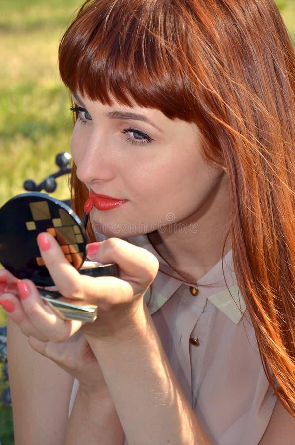 Het roodharige meisje schildert lippen stock fotografie