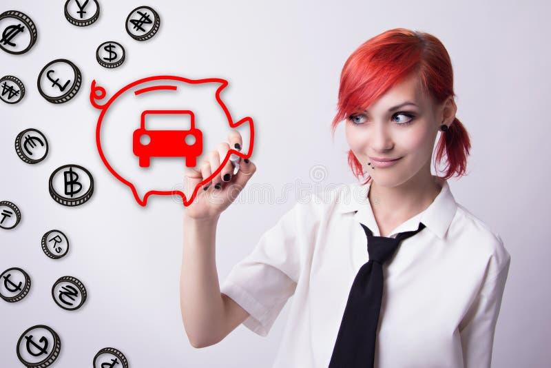 Het roodharige meisje trekt symbolisch auto's en spaarvarken royalty-vrije stock fotografie