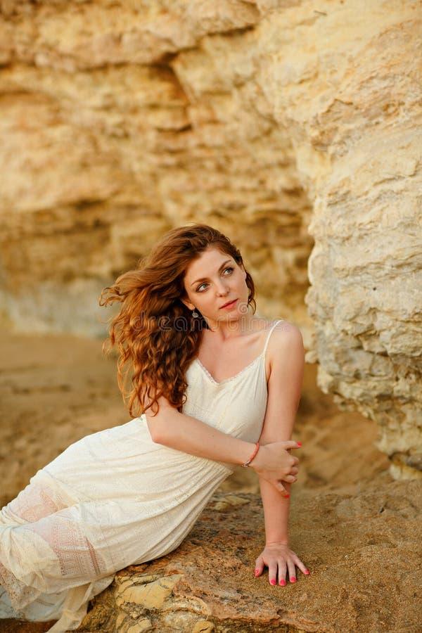 Het roodharige sensuele meisje in witte kledingszitting op de rotsen stock afbeeldingen