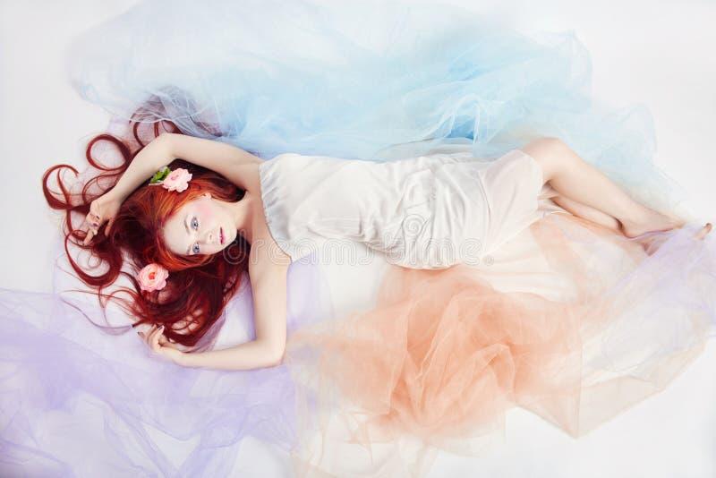 Het roodharigemeisje in lichte luchtige gekleurde kleding ligt op de vloer witte achtergrond Mooie bloemen in meisjeshaar Romanti stock afbeelding