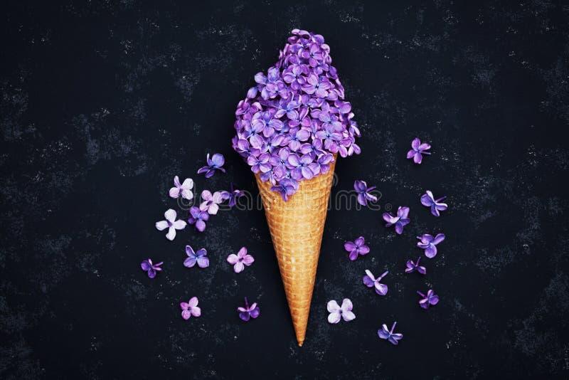 Het roomijs van lilac bloemen in wafelkegel op zwarte achtergrond van hierboven, mooie bloemenregeling, uitstekende vlakke kleur, stock foto's