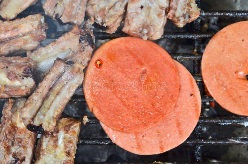 Het roosteren van Bologna en varkensvlees scheurt op het fornuis stock foto's