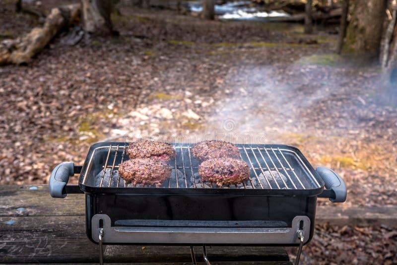 Het roosteren van burgers op de grill van de Houtskoolbarbecue op het hout stock foto