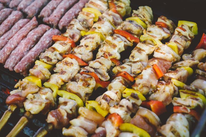 Het roosteren van de vleespennen en de kebab van het kippenvlees met groenten bij de grill van de barbecuehoutskool royalty-vrije stock foto's