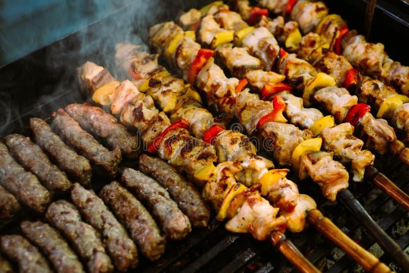 Het roosteren van de vleespennen en de kebab van het kippenvlees met groenten bij de grill van de barbecuehoutskool royalty-vrije stock afbeelding