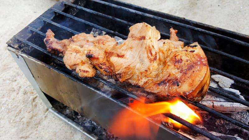 Het roosteren van dunne varkenskoteletten op vlam stock afbeelding