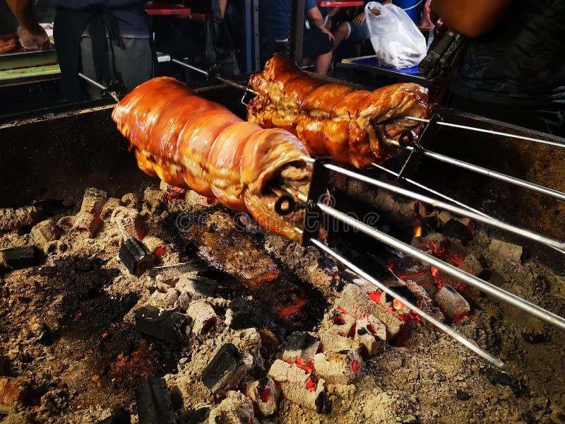 Het roosteren van heerlijke varkenskoteletten in een open houten brand stock fotografie