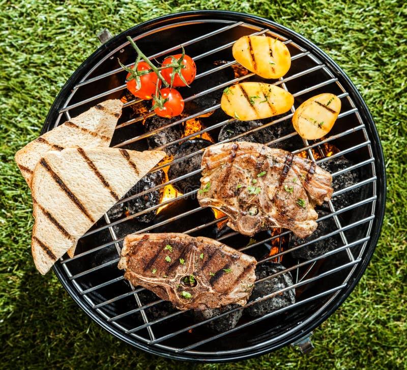 Het roosteren van lamskoteletten en groenten op BBQ stock foto's