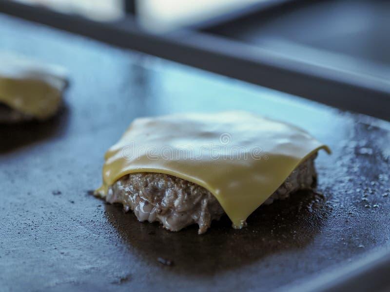 Het roosteren van rundvlees en chese in pan stock foto's
