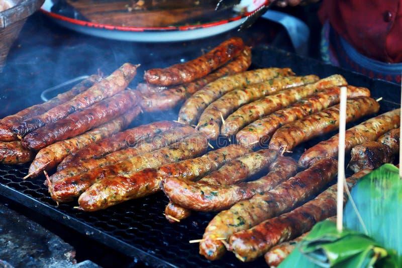 Het roosteren van Thaise worsten bij de barbecuegrill BBQ in de tuin Beierse worsten royalty-vrije stock foto's