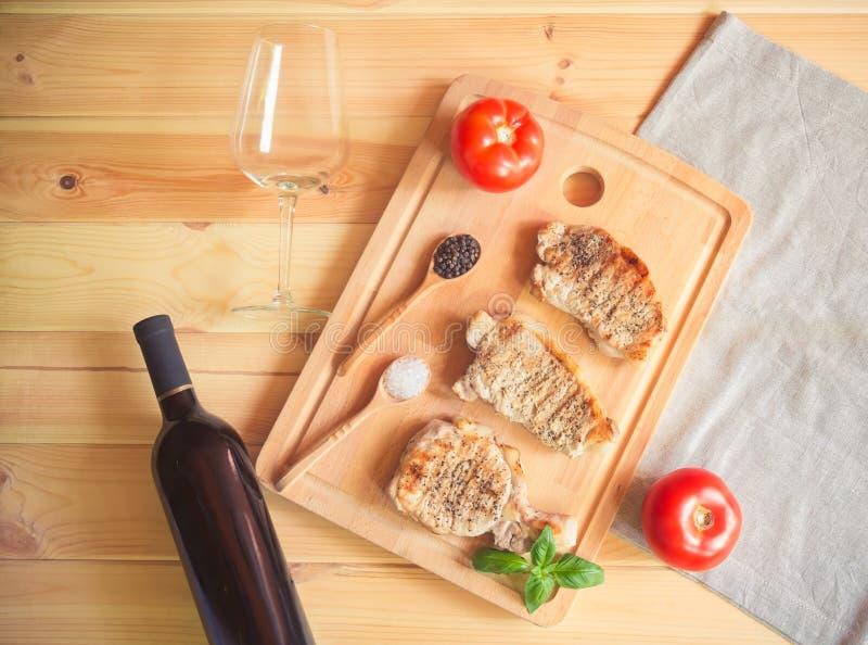 Het roosteren van varkensvleeslapjes vlees op scherpe raad, fles rode wijn en leeg wijnglas royalty-vrije stock foto