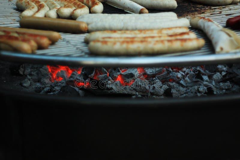 Het roosteren van worsten bij de barbecuegrill, straatvoedsel, het festival van het de zomervoedsel Selectieve nadruk royalty-vrije stock afbeelding
