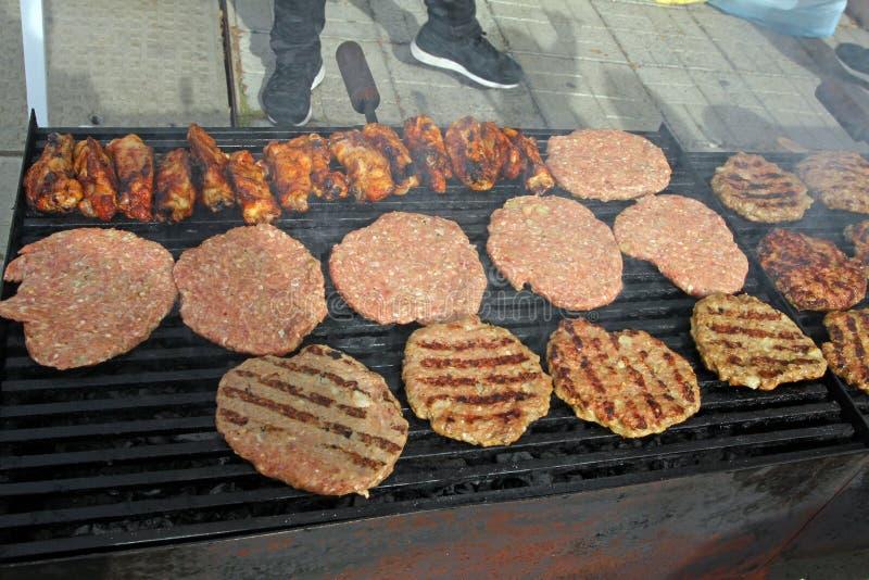 Het roosteren van worsten, burgers, varkensvleeslapje vlees bij de grill van het barbecuesgas voor partij Hotdogs, worsten en ham royalty-vrije stock fotografie