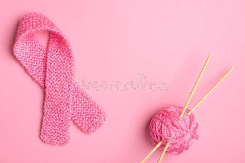 Het roze de Voorlichtingssymbool van Borstkanker breide in roze garen met bal van garen en naalden aan kanten met centrumruimte o stock foto