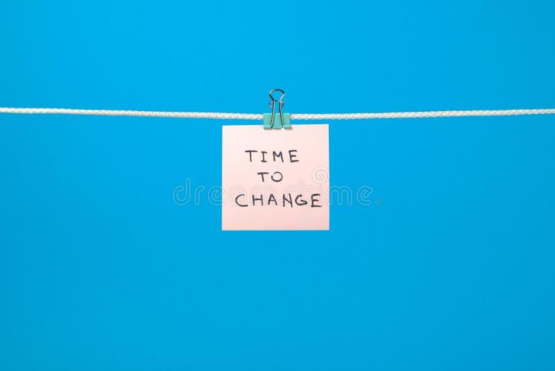 Het roze document nota hangen op het koord met teksttijd te veranderen stock foto