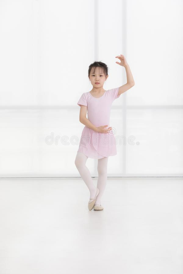 Het roze kleedde Aziatisch meisje in een ballet stelt stock fotografie