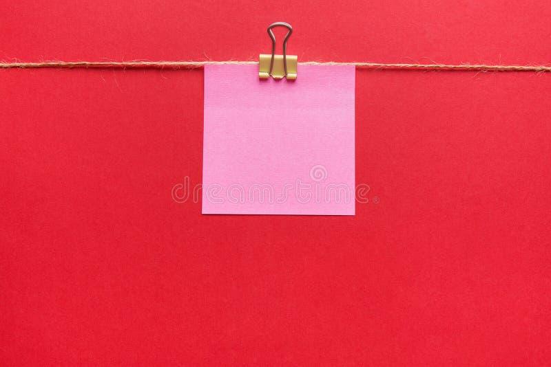 Het roze kleverige nota hangen op paperclip op streng op donkerrode achtergrond Het memorandummodel van het aankondigingsbericht  royalty-vrije stock foto's