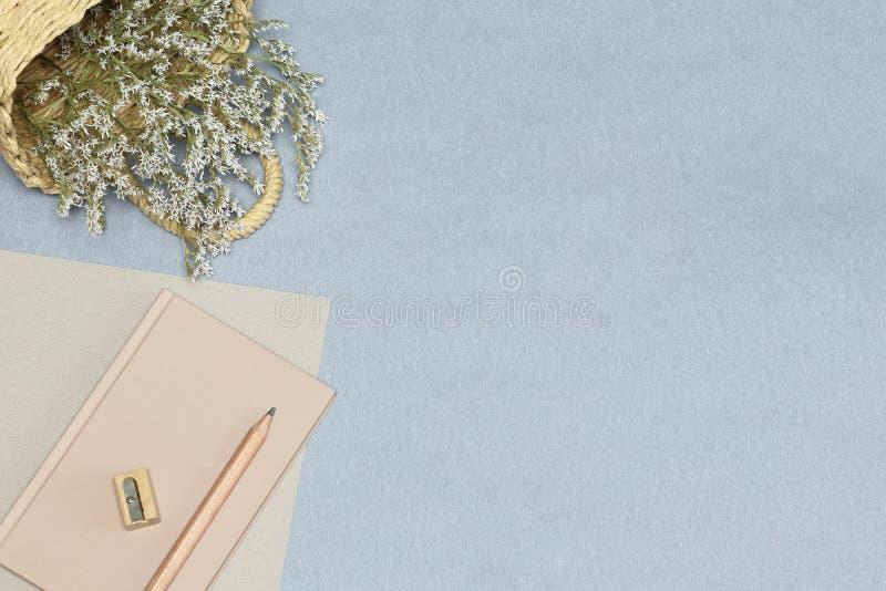 Het roze notitieboekje, het houten potlood & de slijper, mand met bloemen op het blauwe bureau stock foto