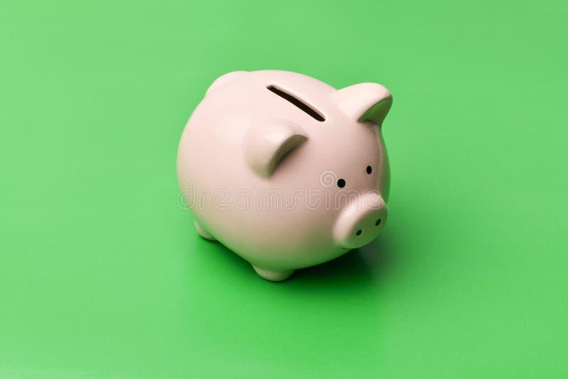 Het roze spaarvarken in de vorm van een varken bevindt zich in het centrum op a stock foto's