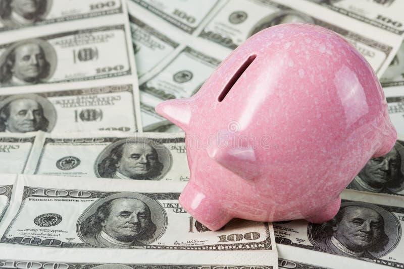 Het roze spaarvarken leunde aan de dollars, alsof overwegend hen, het concept financiën en besparingen stock foto's