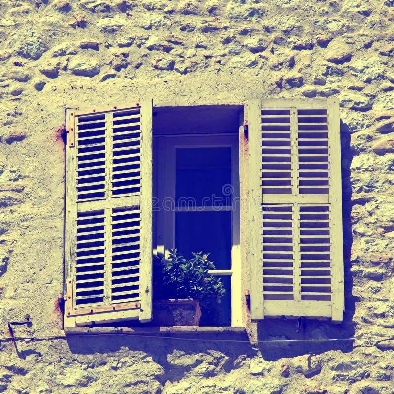 Het rustieke venster met oude houten blinden in steen landelijk huis, blijkt royalty-vrije stock fotografie