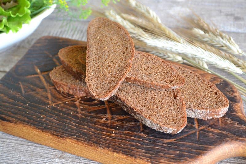 Het rustieke zwarte brood en de tarwe op een oude wijnoogst planked houten lijst royalty-vrije stock fotografie