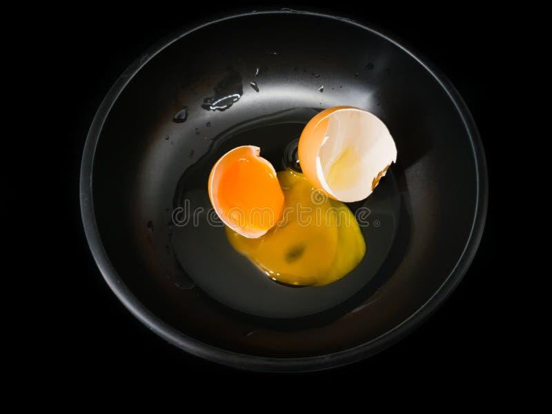 Het rustige beeld van een ruw organisch ei barstte open op een zwarte kop en een zwarte achtergrond stock afbeelding