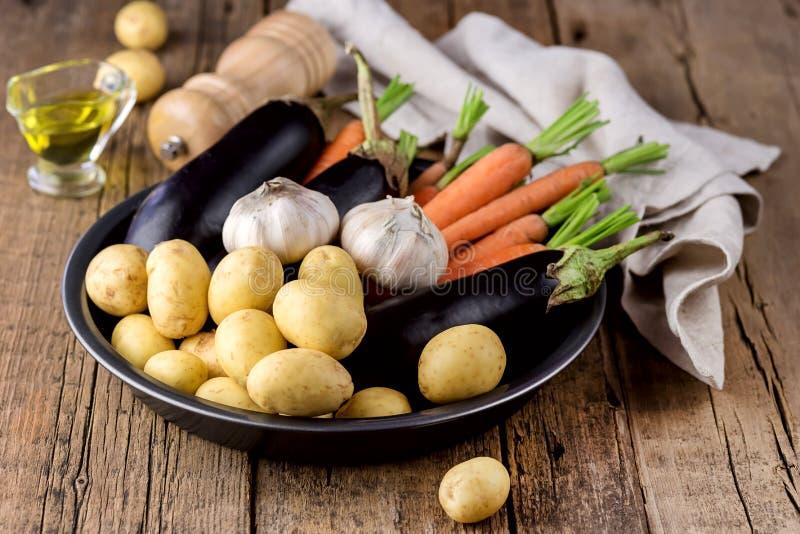 Het ruwe Jonge Knoflook en de Aubergine van de Aardappelswortel op Zwarte Plaatverscheidenheid van Rauwe groenten klaar Cook Fres stock foto's