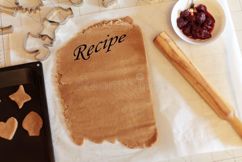 Het ruwe koekjesdeeg met plaats voor recept, sommige koekjesvormen, koekjes klaar aan oven, houten rol en kom met aardbei blokkee royalty-vrije stock foto's