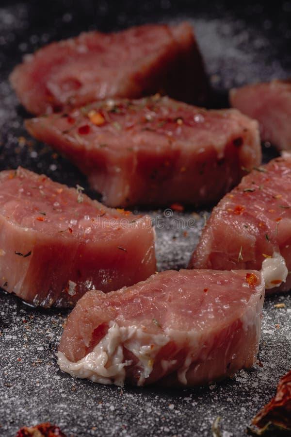 Het ruwe vlees van varkensvleesmedalions Verse lapjes vlees op zwarte achtergrond 45 graad royalty-vrije stock afbeeldingen