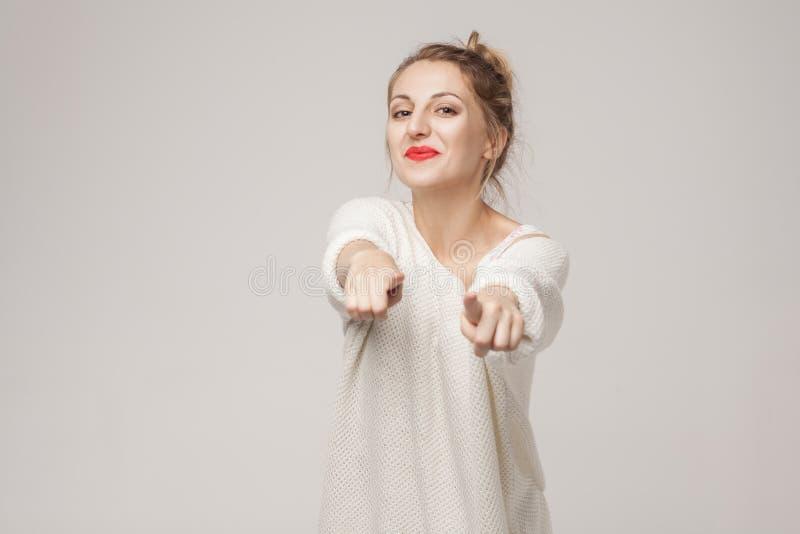 Het ` s voor u! De vrouw die van het gelukblonde vinger richten op camera stock afbeelding