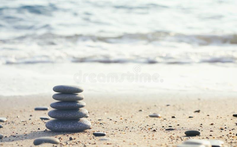 Het saldo van de stenenpiramide op zand en vage achtergrond Het thema van de kuuroordtherapie Overzeese Mening Strand De tuin van royalty-vrije stock afbeelding