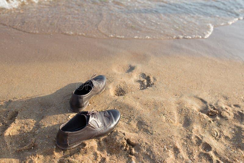 Het het Saldoconcept van het het werkleven, Zakenman gaat zijn Werkende Schoenen van start en verlaat het op het Zandstrand voor  stock foto